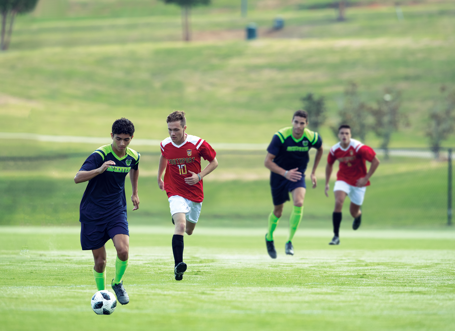 A soccer field with two opponents chasing after two players in the front